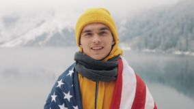 Portrait of a young attractive man with American flag in winter clothes. Hiking man wearing yellow winter clothes looks. At the camera and smiles. Beautiful stock footage