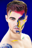Portrait of young attractive man with colored face paint on blue background. Professional Makeup Fashion. ffantasy art Stock Photography
