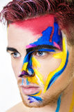 Portrait of young attractive man with colored face paint on white background. Professional Makeup Fashion. ffantasy art Royalty Free Stock Image