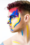 Portrait of young attractive man with colored face paint on white background. Professional Makeup Fashion. ffantasy art Stock Images