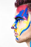 Portrait of young attractive man with colored face paint on white background. Professional Makeup Fashion. ffantasy art Stock Image