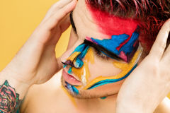 Portrait of young attractive man with colored face paint on yellow background. Professional Makeup Fashion. ffantasy art Stock Images