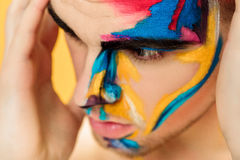 Portrait of young attractive man with colored face paint on yellow background. Professional Makeup Fashion. ffantasy art. Portrait of young attractive man with royalty free stock photos
