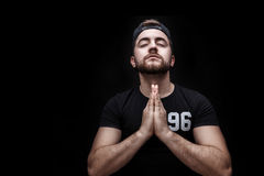 Portrait of young attractive man with dark hair wearing black shirt in yoga pose on black background. Royalty Free Stock Photo