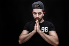 Portrait of young attractive man with dark hair wearing black shirt in yoga pose on black background. Stock Photo