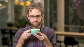 Portrait of young attractive man drinking tasty hot cappuccino after hard working day and smiling with pleasure stock footage