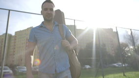 Portrait of young attractive man with guitar standing near a metal fence. Young cheerful man with guitar during sunny day, urban background stock footage