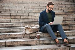 Portrait of young attractive man using laptop computer. While sitting on stairs outdoors Royalty Free Stock Images