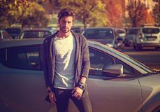 Handsome young man next to car in white shirt. Portrait of young attractive man in white shirt leaning on his new stylish polished car outdoor in city street Stock Photos