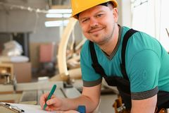 Portrait of young attractive man in work. Clothes and yellow helmet crossed arms smiling at shop for manufacturing furniture and details home interior royalty free stock images