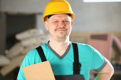 Portrait of young attractive man in work. Clothes and yellow helmet crossed arms smiling at shop for manufacturing furniture and details home interior royalty free stock photos