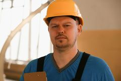 Portrait of young attractive man in work. Clothes and yellow helmet crossed arms smiling at shop for manufacturing furniture and details home interior royalty free stock photography