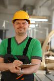 Portrait of young attractive man in work. Clothes and yellow helmet crossed arms smiling at shop for manufacturing furniture and details home interior royalty free stock photo