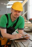 Portrait of young attractive man in work. Clothes and yellow helmet crossed arms smiling at shop for manufacturing furniture and details home interior stock photography