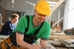 Portrait of young attractive man in work. Portrait of young attractive men in work clothes and yellow helmet crossed arms smiling at shop for manufacturing royalty free stock photo