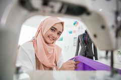 Attractive muslim woman fashion designer. Portrait of young attractive muslim woman fashion designer in her workshop smiling to camera Stock Photos