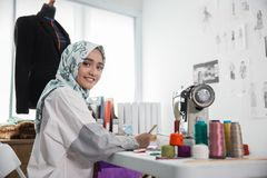 Attractive muslim woman fashion designer. Portrait of young attractive muslim woman fashion designer in her workshop smiling to camera Stock Images