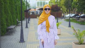 Portrait young attractive muslim woman visually impaired with a walking cane in the park stock video footage