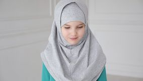 Young muslim teen girl in hijab shyly looking at camera and smiling. stock footage