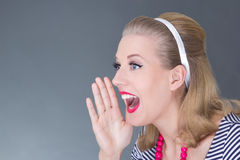 Young attractive pinup girl in striped dress screaming. Portrait of young attractive pinup girl screaming over grey royalty free stock image