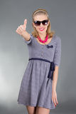 Young attractive pinup girl in sunglasses thumbs up Stock Photography