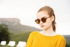 Portrait of a young attractive serious girl in sunglasses against the background of rocks and sky. Seriousness in the stock photography