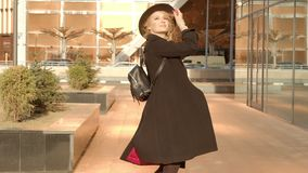 Portrait young attractive smile woman in hat and black coat gulyayet po ulitse walking down the street at city center stock video