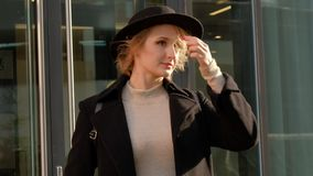 Portrait young attractive smile woman in hat and black coat look at camera at city center feel happy fashion girl face stock footage