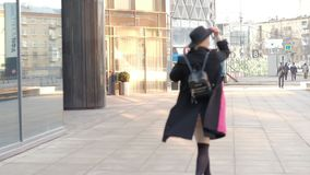Portrait young attractive smile woman in hat and black coat walking down the street at city center feel happy fashion stock footage