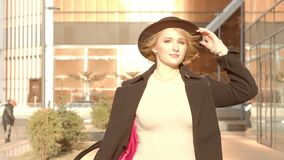 Portrait young attractive smile woman in hat and black coat walking down the street at city center feel happy fashion stock video footage
