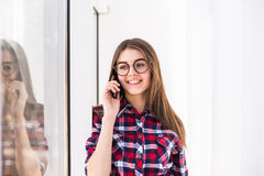 Portrait of young attractive smiling caucasian girl talking per mobile phone. Stock Images
