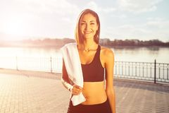 Portrait young smiling woman with white towel. Portrait young attractive smiling fit woman with white towel resting after workout sport exercises outdoors on a Royalty Free Stock Photography