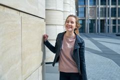 Portrait of young attractive smiling happy girl in a leather jacket and jeans against the backdrop of modern urban architecture. And columns. The concept of Royalty Free Stock Image