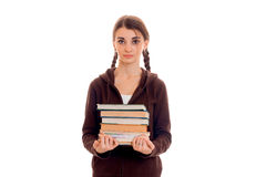 Portrait of young attractive student girl in brown sport clothes with a lot of books in hands isolated on white royalty free stock image