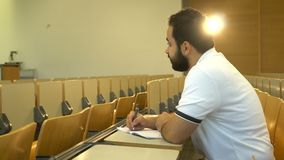 Portrait of young attractive student sitting in lecture hall, Magdeburg, Germany. 01.09.2018 stock video