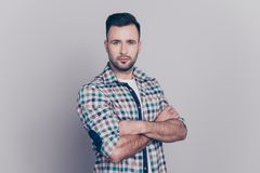 Portrait of young attractive stunning man having his hands cross. Ed, looking at camera with serious expression, standing over grey background Royalty Free Stock Photography