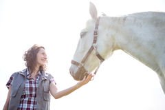 Portrait of a young attractive veterinary in fields with horse Stock Image