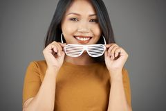 Attractive woman putting in glasses royalty free stock photography
