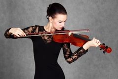 Portrait of a young attractive violinist woman in a black evenin Royalty Free Stock Photos
