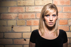 Portrait of Young Attractive Woman Against Brick Wall Royalty Free Stock Photography