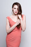 Portrait of a young attractive woman with beautiful long brown hair. She wears a coral dress and diamond earrings. Stock Photos