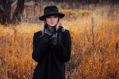 Portrait of young attractive woman in black coat and hat. Autumn landscape, dry grass Stock Image