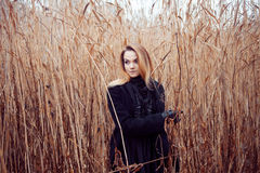 Portrait of young attractive woman in black coat and hat. Autumn landscape, dry grass Royalty Free Stock Image