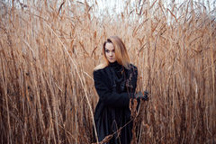 Portrait of young attractive woman in black coat and hat. Autumn landscape, dry grass Stock Photography