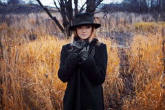 Portrait of young attractive woman in black coat and hat. Lifts collar coat. Autumn landscape, dry grass Royalty Free Stock Photo