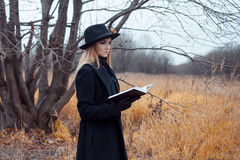Portrait of young attractive woman in black coat and hat. She's one in a field reading book, autumn landscape, dry grass Royalty Free Stock Photos
