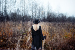 Portrait of young attractive woman in black coat and hat. She's one in a field reading book, autumn landscape, dry grass Stock Photo