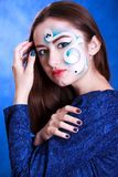 Portrait of a young attractive woman with a blue face art Stock Photos