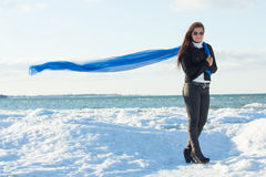 Portrait of young woman with blue scarf on winter beach Stock Photography