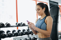 Portrait of young and attractive woman in blue top in gym. stock photo